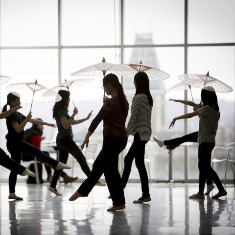 international students dancing with parasols