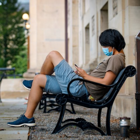 Student sitting on bench and wearing a mask
